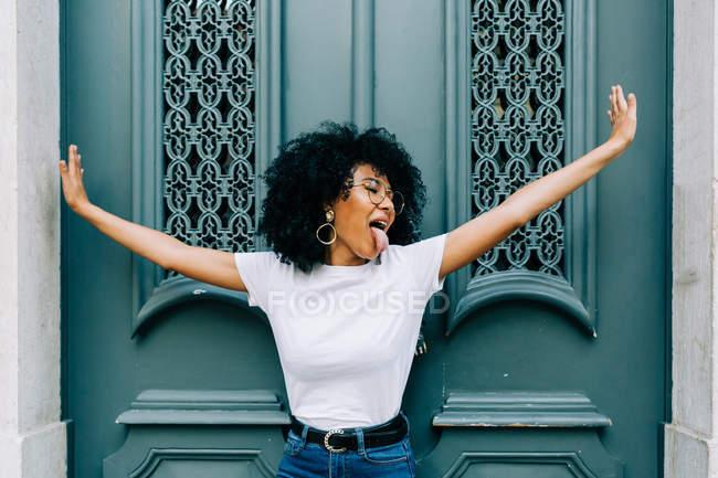 Молода Африканська американська жінка, що стоїть з закритими очима зелені дерев'яні двері і стирчить язик — стокове фото