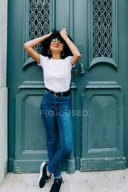Bella donna etnica in t-shirt bianca e jeans appoggiati sulla porta verde — Foto stock