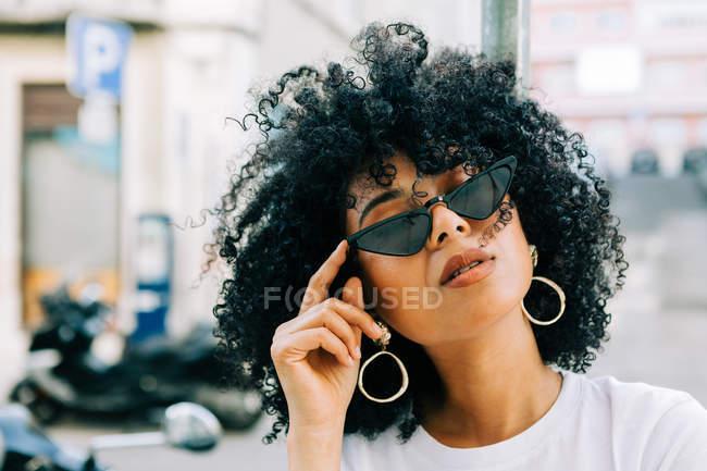 Mulher muito étnica em t-shirt branca e com cabelo encaracolado preto sobre óculos pretos — Fotografia de Stock