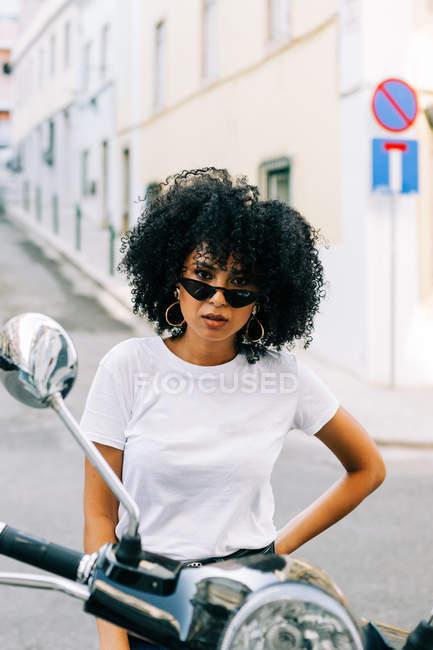 Молодая афроамериканка с черными вьющимися волосами сидит на мотоцикле и смотрит в камеру через солнцезащитные очки — стоковое фото