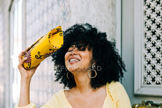 Cheerful young woman with lush curly hair and closed eyes holding fashion bag in hand and laughing — Stock Photo