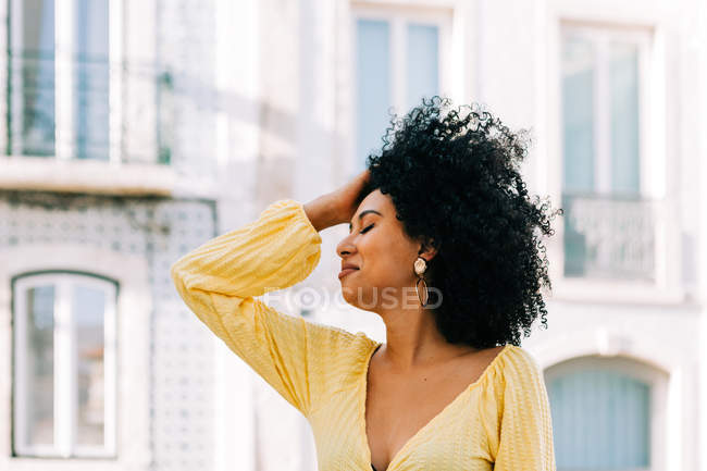 Pretty ethnic woman with black curly hair looking away on street — Stock Photo