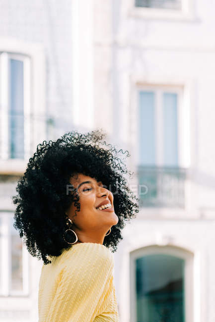 Pretty ethnic woman with black curly hair looking away laughing on street — Stock Photo