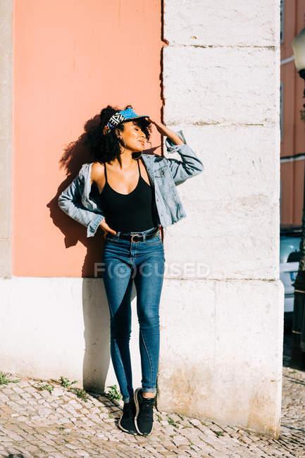 Donna alla moda in jeans e canotta in piedi con gli occhi chiusi e appoggiata al muro nella giornata di sole — Foto stock