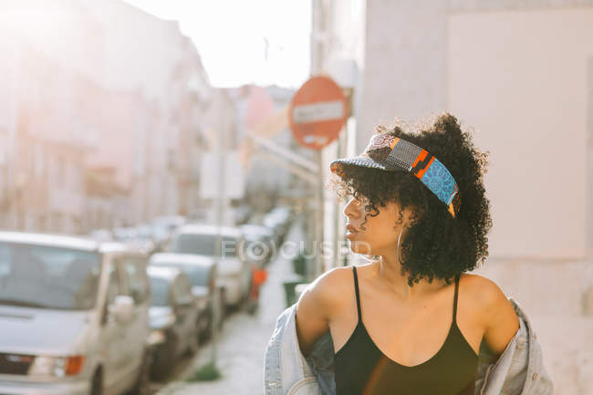 Fashionable African American woman in tank top and unbuttoned denim jacket standing on sidewalk and looking away — Stock Photo