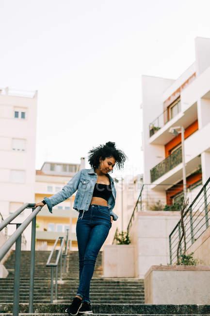 Modische afrikanisch-amerikanische Frau in bauchfreiem Top und Jeans geht die Treppe hinunter — Stockfoto