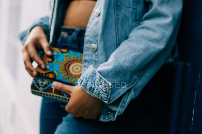African American woman in jeans and denim jacket standing with trendy colorful clutch in hand — Stock Photo