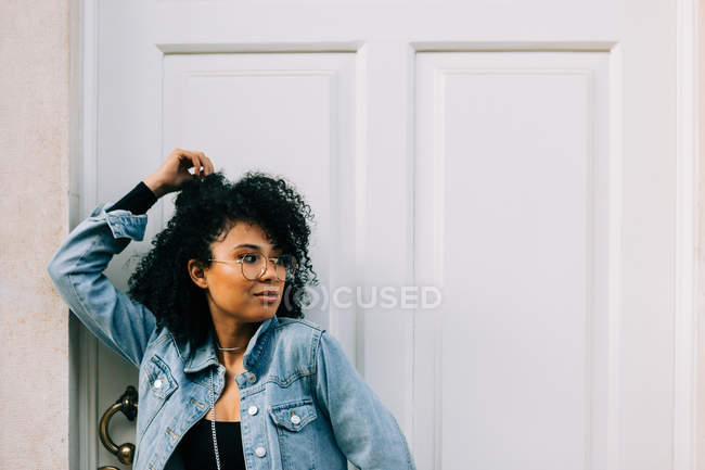 Trendy African American woman in black crop top and jeans standing by door and looking at camera — Stock Photo