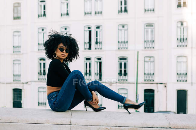 Young trendy African American woman in jeans and crop top sitting on stone parapet and looking over sunglasses — Stock Photo