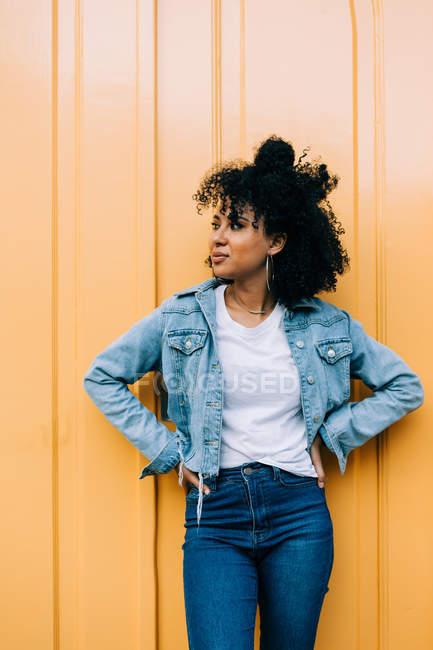 Jeune femme d'Afro-américain dans des jeans et la veste de denim se penchant sur la porte jaune et regardant loin — Photo de stock