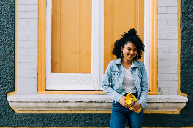 Trendy ethnic woman in jeans and denim jacket holding fashion handbag and leaning on bright windowsill outdoors — Stock Photo
