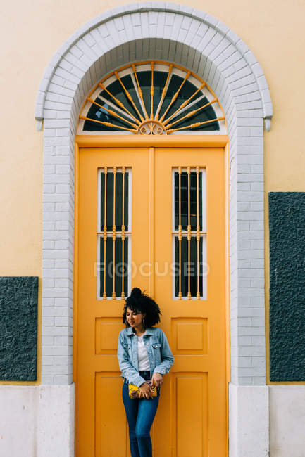 Young African American woman in jeans and denim jacket leaning on yellow door, holding clutch and looking away — Stock Photo
