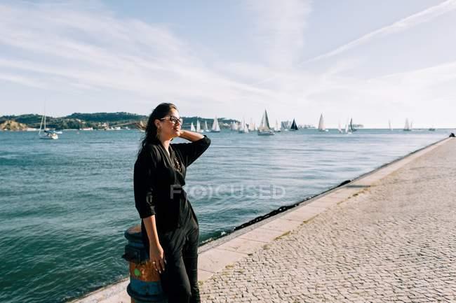 Vista lateral da jovem mulher atraente em roupa preta em pé junto ao mar e apoiada no poste em Lisboa — Fotografia de Stock