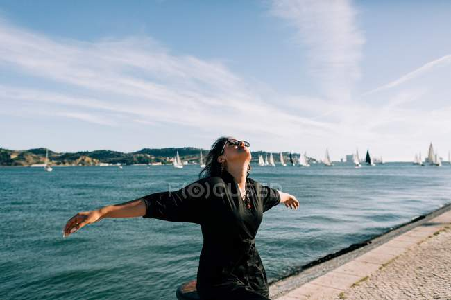 Vista lateral de la joven atractiva mujer en traje negro de pie junto al mar y apoyado en el poste en Lisboa - foto de stock