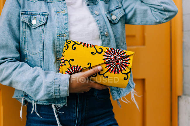 Closeup of woman in jeans and denim jacket leaning on yellow door, holding clutch — Stock Photo