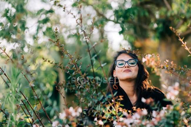 Schöne brünette Frau mit Brille steht zwischen blühenden Büschen im Park und blickt in die Kamera in Lissabon — Stockfoto