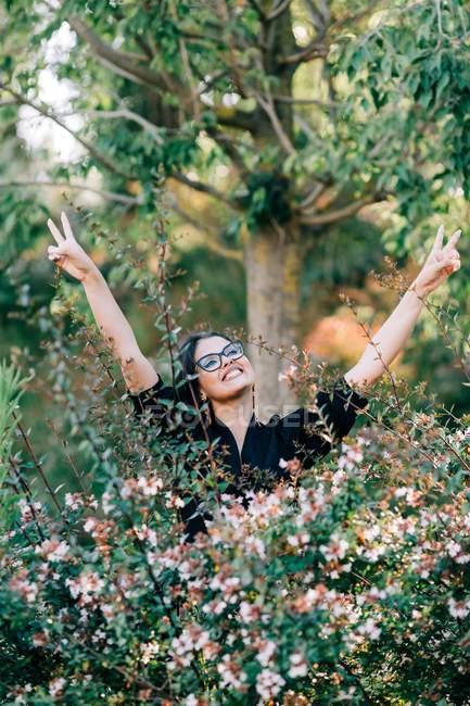 Красивая брюнетка в очках стоит среди цветущих кустов в парке и смотрит вдаль в Лиссабоне — стоковое фото