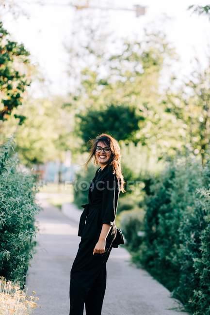 Модная молодая женщина, идущая по мощеной тропинке и наслаждающаяся летним днем в Лиссабоне — стоковое фото