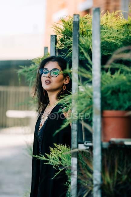 Модная женщина в кружевном топе опирается на стойки с растениями в горшках и смотрит в камеру в Лиссабоне — стоковое фото