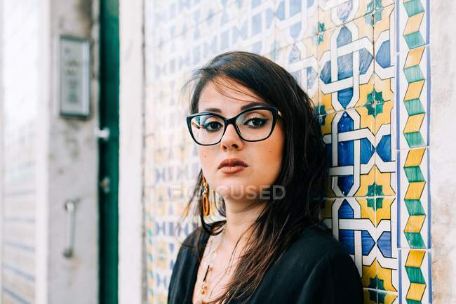Attractive young woman in glasses and black blouse standing by colorful vintage wall and looking at camera in Lisbon — Stock Photo