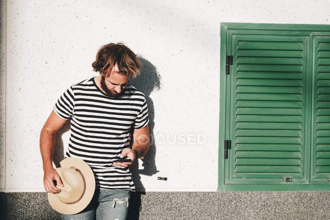Бородатий чоловік в смугастій футболці стоячи на стіні, тримаючи капелюх і за допомогою мобільного телефону в Ла Рестінґа, Ель Йерро — стокове фото