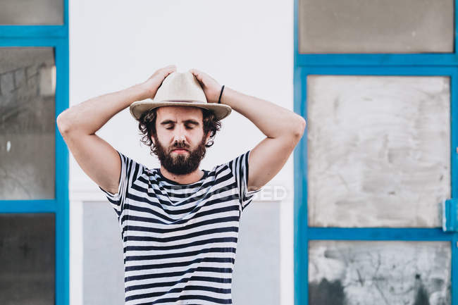 Young male in hat and striped t-shirt with eyes closed — Stock Photo