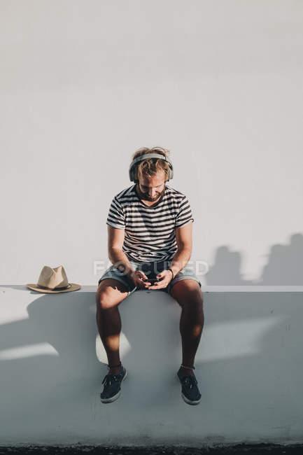 Jovem homem sentado com smartphone e fones de ouvido — Fotografia de Stock