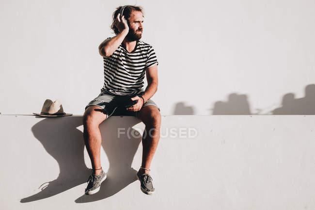 Jovem com cabelo encaracolado sentado em aterro com smartphone e fones de ouvido — Fotografia de Stock