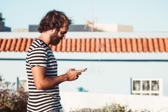 Jovem do sexo masculino andando com telefone celular — Fotografia de Stock