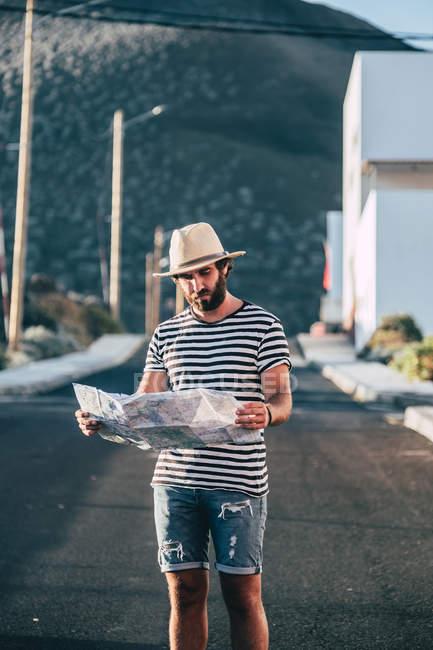 Männlicher Reisender steht mit Karte auf Straße — Stockfoto