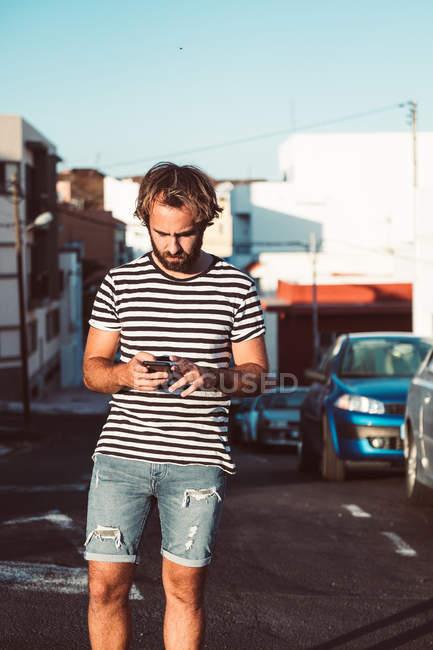 Jovem do sexo masculino caminhando com telefone celular na rua urbana — Fotografia de Stock