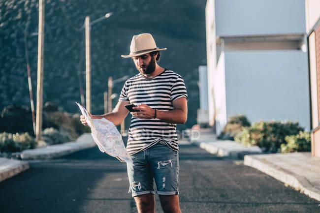 Мужчина-путешественник, стоящий с картой и смартфоном — стоковое фото