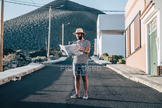 Viaggiatore maschio in cappello in piedi con mappa in città — Foto stock