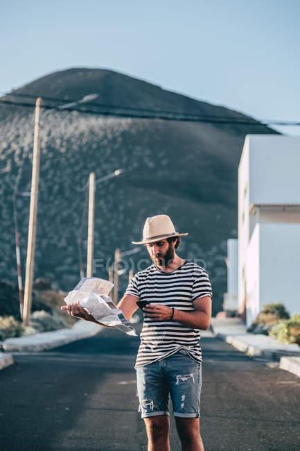 Jovem na moda procurando destino no mapa enquanto caminhava na estrada em La Restinga, El Hierro — Fotografia de Stock