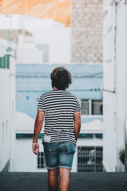 Visão traseira do turista masculino caminhando na estrada deserta — Fotografia de Stock