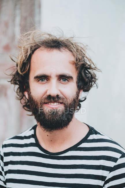 Jovem barbudo sorrindo e olhando para a câmera na cidade — Fotografia de Stock