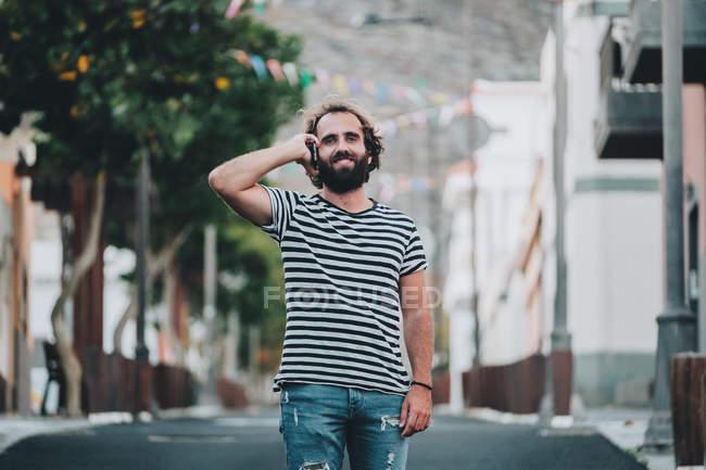 Junger Mann zu Fuß unterwegs und telefoniert mit Handy — Stockfoto