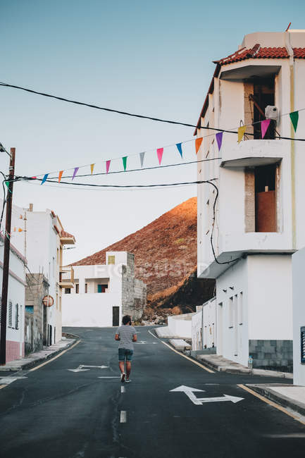 Rear view of man walking on deserted road in town — Stock Photo