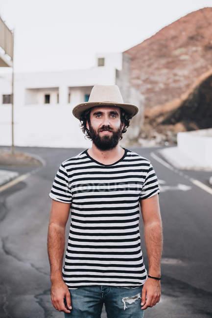 Jovem elegante em camiseta listrada em pé na estrada e sorrindo na câmera em La Restinga — Fotografia de Stock