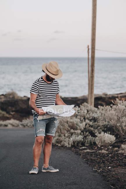 Voyageur mâle restant avec la carte dans la campagne — Photo de stock