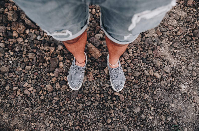 Cropped male legs in jeans shorts on road from above — Stock Photo