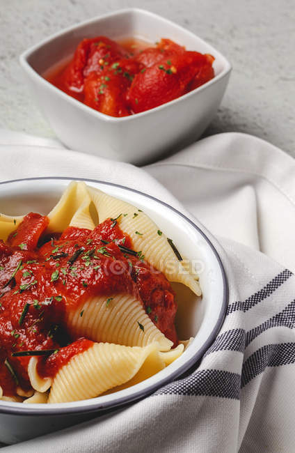 Delicious conchiglie pasta sprinkled with basil and red tomato sauce served on white plate — Stock Photo