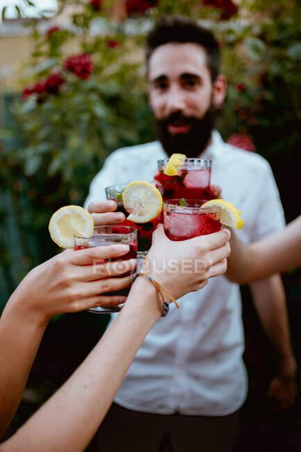 Веселі друзі чіпляються за скло на вечірці. — стокове фото
