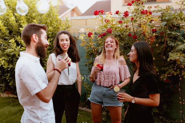 Group of cheerful friends clinking glasses at party — Stock Photo