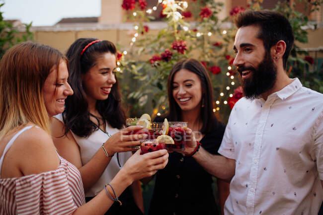 Grupo de jovens amigos sorridentes hipster clinking copos com bebidas de baga coloridas na festa de verão quintal — Fotografia de Stock