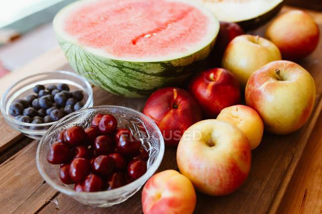 Deliciosas frutas y bayas de verano sobre una mesa de madera rústica - foto de stock