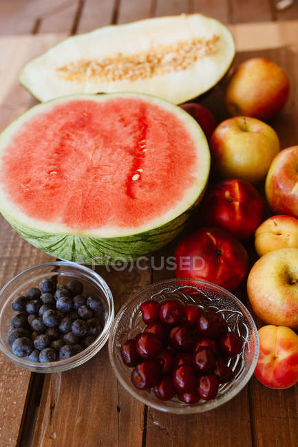 Delicious summer fruits and berries on rustic wooden table — Stockfoto