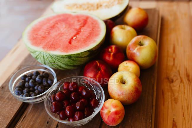 Вкусные летние фрукты и ягоды на деревенском деревянном столе — стоковое фото