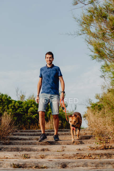 Happy man walking with dog along rural pathway — Stock Photo