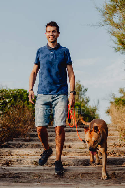 Cheerful casual man keeping on leash playful brown dog while walking along pathway in rural countryside in daylight — Stock Photo